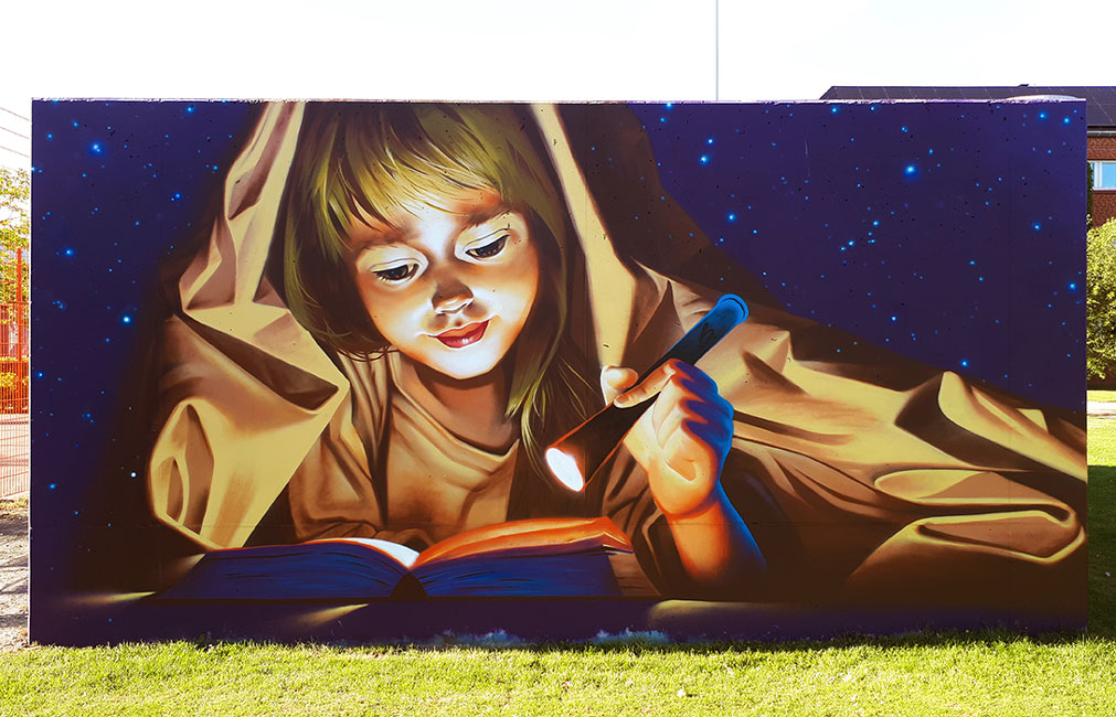 Girl reading under a blanket, in the night, mural by Bogdan Scutaru
